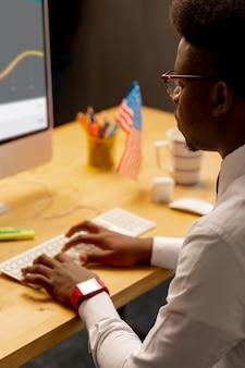 Intelligenter hart arbeitender mann, der vor dem computer sitzt, während er den text darauf tippt