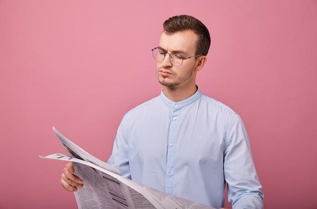 Intelligenter herr in einem hellblauen hemd in gläsern mit einer zeitung in den händen
