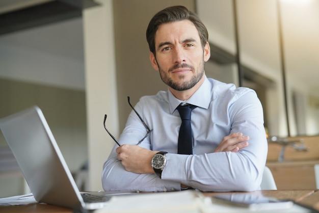Intelligenter hübscher geschäftsmann im büro mit dem laptop, der kamera betrachtet