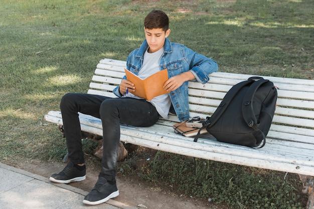 Intelligenter jugendjunge, der auf der bank studiert im park sitzt