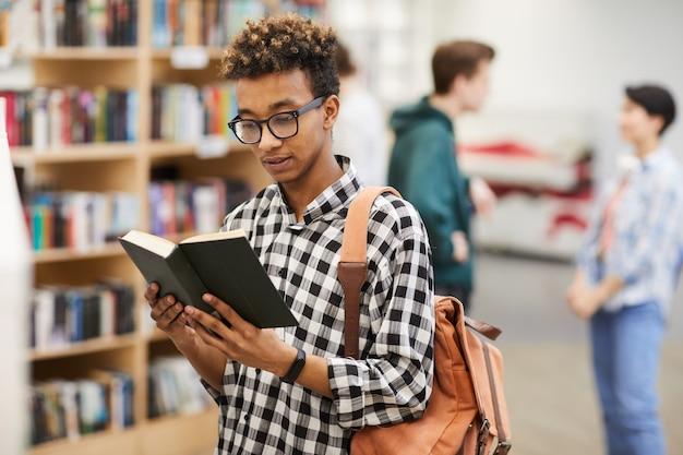 Intelligenter kerl, der buch in der bibliothek liest