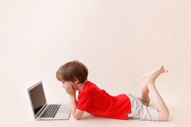 Intelligenter kleiner junge mit laptop in freizeitkleidung. konzept der online-lerntechnologie.