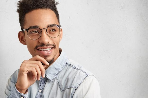 Intelligenter kluger männlicher student trägt runde brille, denkt über zukünftiges projekt nach,