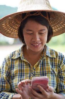 Intelligenter landwirt des porträts, der smartphone im unschärfeleisfeld verwendet