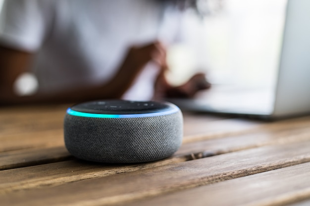 Intelligenter lautsprecher platziert auf tisch nahe ernte schwarze frau mit laptop zu hause