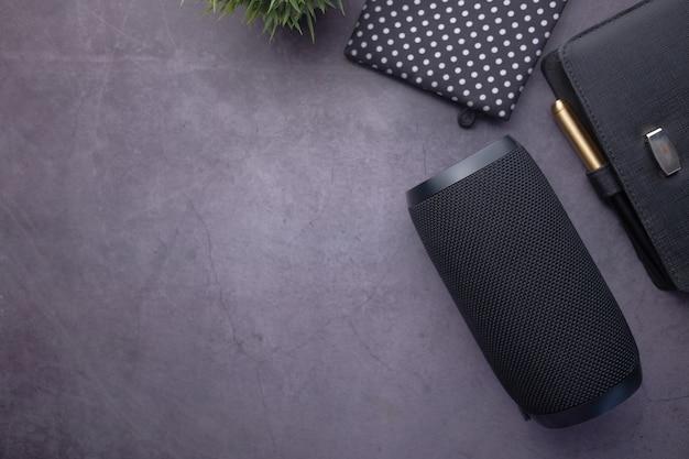Intelligenter lautsprecher und notizblock mit kopierraum auf schwarzem hintergrund