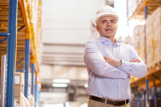 Intelligenter logistikmanager, der einen helm trägt, während er im lager arbeitet