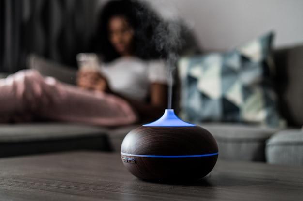Intelligenter luftbefeuchter, der wasserdampf auf tisch nahe sofa mit schwarzer frau zu hause emittiert