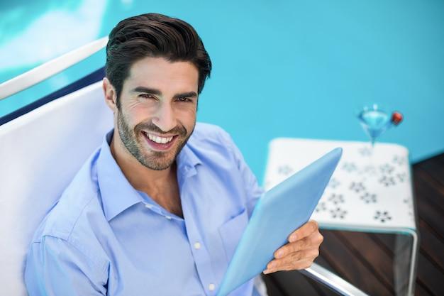 Intelligenter mann, der digitale tablette nahe pool verwendet