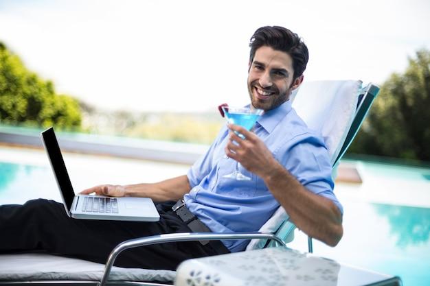 Intelligenter mann, der martini bei der anwendung des laptops nahe pool hat