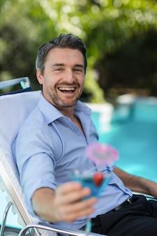 Intelligenter mann, der martini-glas bei der entspannung im sonnenruhesessel hält