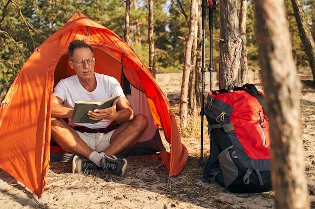 Intelligenter reifer mann sitzt im zelt und liest literatur nach nordic walking im wald