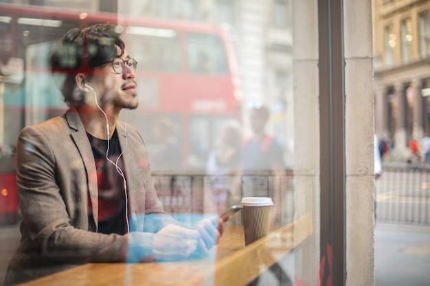 Intelligenter schauender mann, der in einem café, hörend zu etwas an seinem telefon sitzt