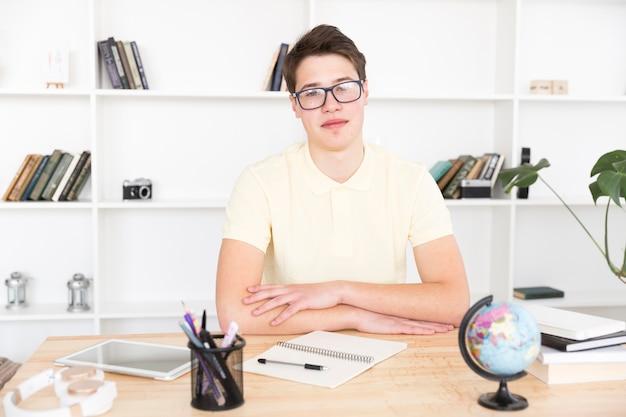 Intelligenter student in den gläsern, die am schreibtisch sitzen
