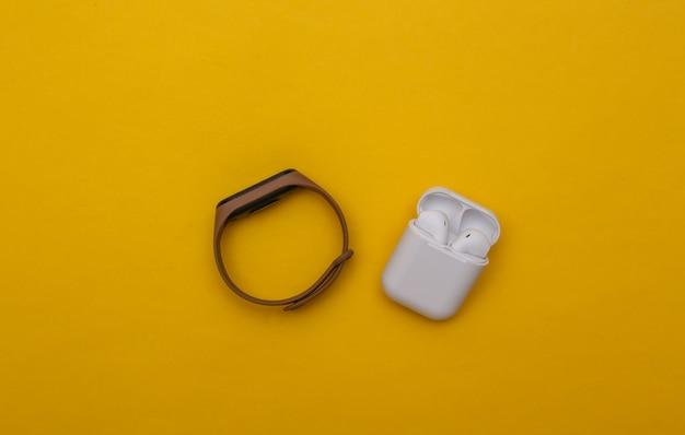 Intelligentes armband und drahtlose kopfhörer auf gelbem hintergrund. moderne gadgets für outdoor-aktivitäten und sport. ansicht von oben