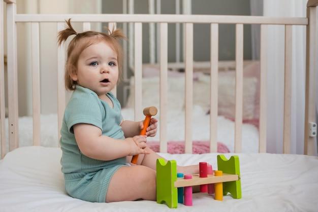 Intelligentes baby sitzt auf einem babybett und spielt ein lernspielzeug