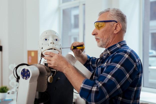 Intelligentes engineering. netter alter mann, der einen schraubenzieher hält, während er einen roboter baut
