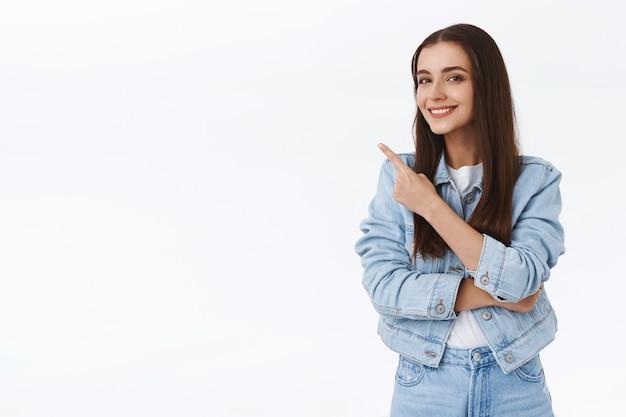 Intelligentes, gut aussehendes, kreatives junges brünettes mädchen, das ratschläge gibt, auf die obere linke ecke zeigt, promo vorschlägt, erfreut lächelt, ein produkt genehmigt, weißer hintergrund steht
