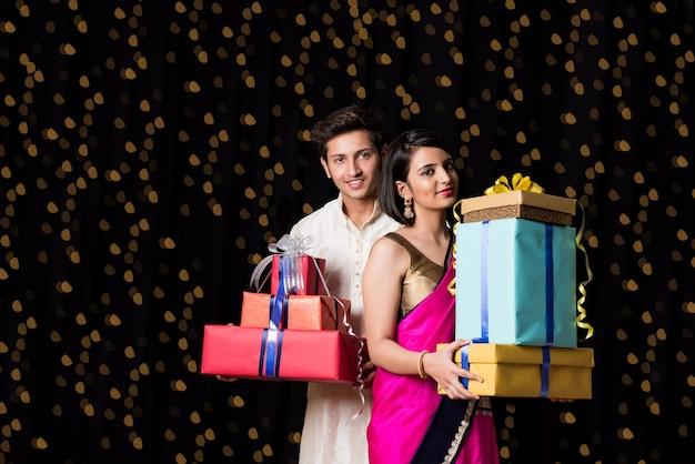 Intelligentes indisches paar, das mit geschenkboxen auf diwali-festival oder hochzeitszeremonie steht