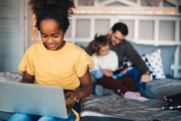 Intelligentes jugendliches schulmädchen, das ihre hausaufgaben mit digitalem notizbuch zu hause macht. kind, das geräte zum lernen verwendet. bildung und lernen für kinder.