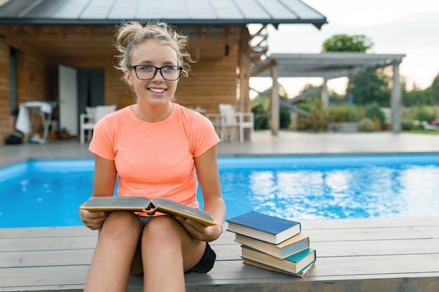 Intelligentes junges mädchen im lesebuch der brille, teenager nahe haus, außenpool und rasen