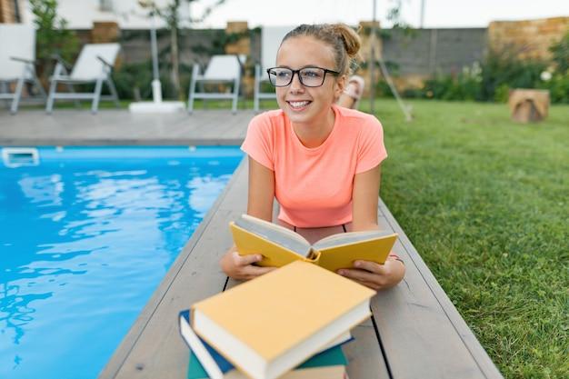 Intelligentes junges mädchen in den gläsern, die buch durch pool lesen