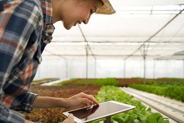 Intelligentes junges nettes asiatisches landwirtmädchen, das tablette verwendet, um qualität und quantität des gemüses im wasserkulturbauernhof zu überprüfen