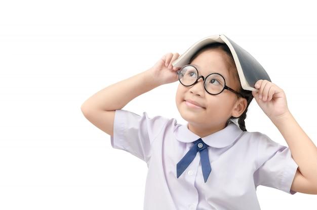 Intelligentes kleines asiatisches mädchen, das mit buch auf kopf denkt