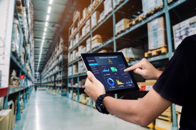 Intelligentes lagerverwaltungssystem. arbeiterhände, die tablet auf unscharfem lager als hintergrund halten