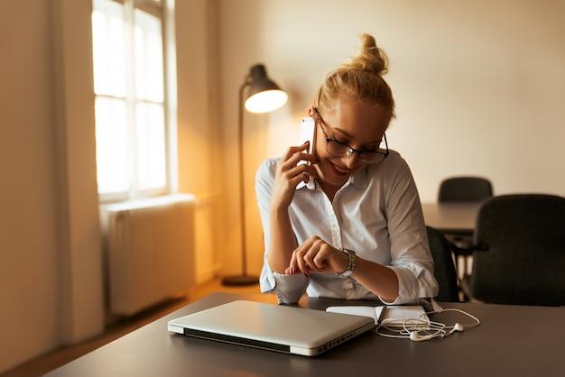 Intelligentes mädchen mit gläsern sprechend am telefon und ihre neue uhr betrachtend