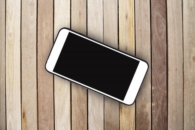 Intelligentes mobiltelefon auf hölzernem hintergrund