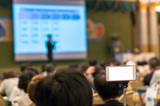 Intelligentes mobiltelefon, das live-streaming zu asiatischem sprecher mit beiläufigem anzug auf der bühne vor tut