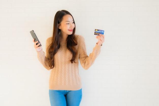 Intelligentes mobiltelefon des schönen jungen asiatischen gebrauches des porträts mit kreditkarte
