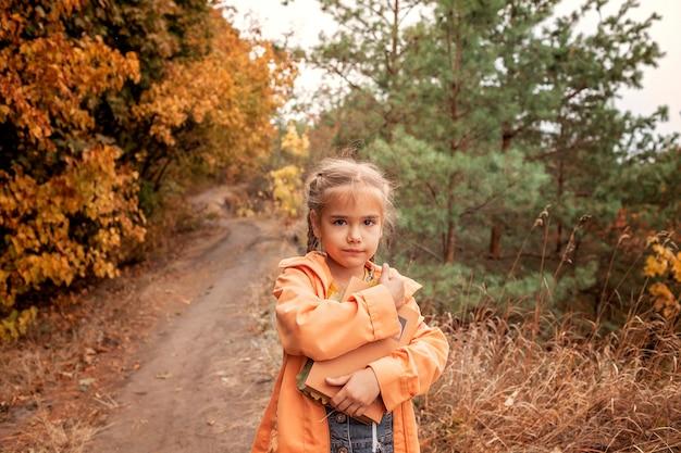 Intelligentes nettes kindermädchen, das ein buch mit trockenen gelben blättern hält