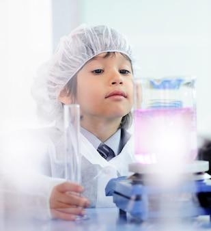Intelligentes nettes kleines männliches kind, das mit reagenzgläsern im wirklichen modernen krankenhauslabor experimentiert