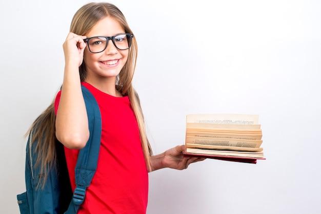 Intelligentes schulmädchen, das mit lehrbuch steht