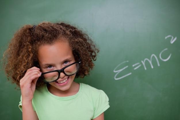 Intelligentes schulmädchen, das über ihren gläsern schaut
