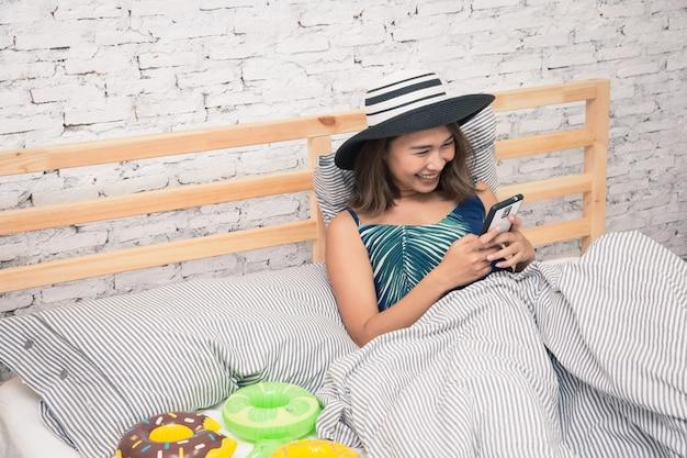 Intelligentes telefon der schönen asiatinrührenden tablette und essen des popcorns auf bett