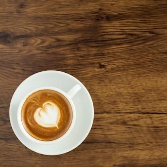 Intelligentes telefon mit lattekunstkaffee auf hölzernem hintergrund