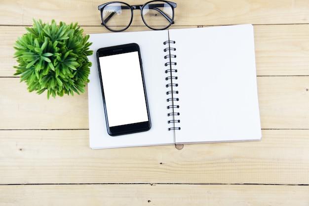 Intelligentes telefon mit leerem bildschirm auf buch