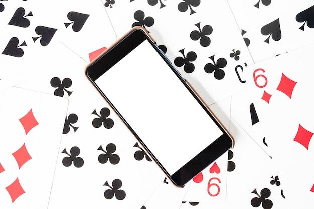 Intelligentes telefon mit weißem schirm auf spielkartehintergrund.