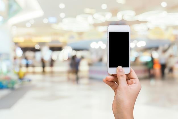 Intelligentes telefon mit weißem schirm in der hand auf verwischt im einkaufszentrumhintergrund, kaufendes on-line-konzept, kaufend durch intelligentes telefon