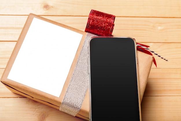 Intelligentes telefon und geschenk auf holztisch