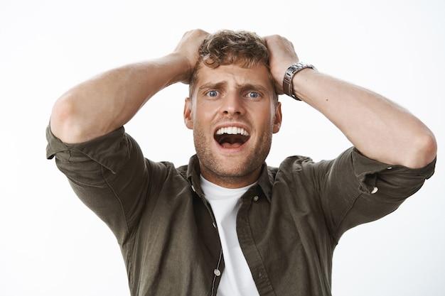 Intensiv schockierter typ in benommenheit mit blauen augen und blonden haaren, die hände am kopf halten, schreien, in panik schreien, ausflippen, fassungslos und unsicher über grauer wand stehen, verängstigt und verängstigt