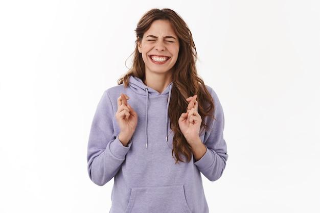Intensive nervöse junge hoffnungsvolle frau augen schließen zähne nervös kreuzen die finger viel glück beten unteres herz williger traum wird wahr und wünscht sich wichtige neuigkeiten vorwegnehmen