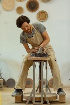 Intensive verarbeitung von ton. fokussierter beschäftigter mann, der auf einer hölzernen töpferscheibe sitzt und neue kreationen produziert