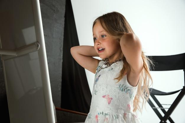 Interaktion von kindern mit erwachsenenwelt. nettes mädchen, das accessoires trägt, um älter zu sein, verspielt und glücklich auszusehen. kleines weibliches model, das zu hause den schmuck der mutter anprobiert. kindheit, stil, traumkonzept.