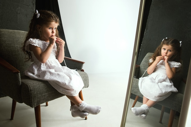 Interaktion von kindern mit erwachsenenwelt. nettes mädchen, das versucht, hell zu machen, um älter zu sein. kleines weibliches model, das zu hause die kosmetik der mutter anprobiert. kindheit, stil, mode, traumkonzept.
