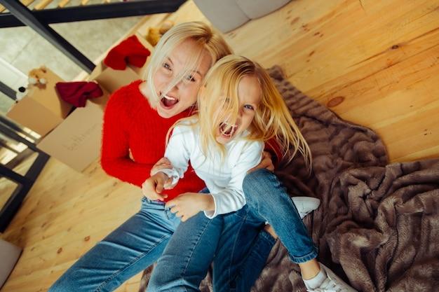 Interaktion zu hause. erfreute weibliche person, die beim spielen mit ihrem kind ein lächeln auf ihrem gesicht behält