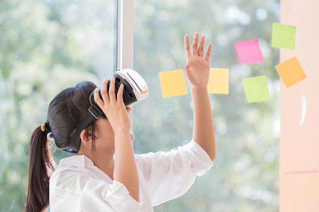 Interaktionskopfhörer der virtuellen realität durch asiatische schöne junge frau, die rührende luft während vr-kastens für das spielen von zukünftigen medien des spielsimulators trägt. digitales futuristisches innovationsgerätkonzept der technologie